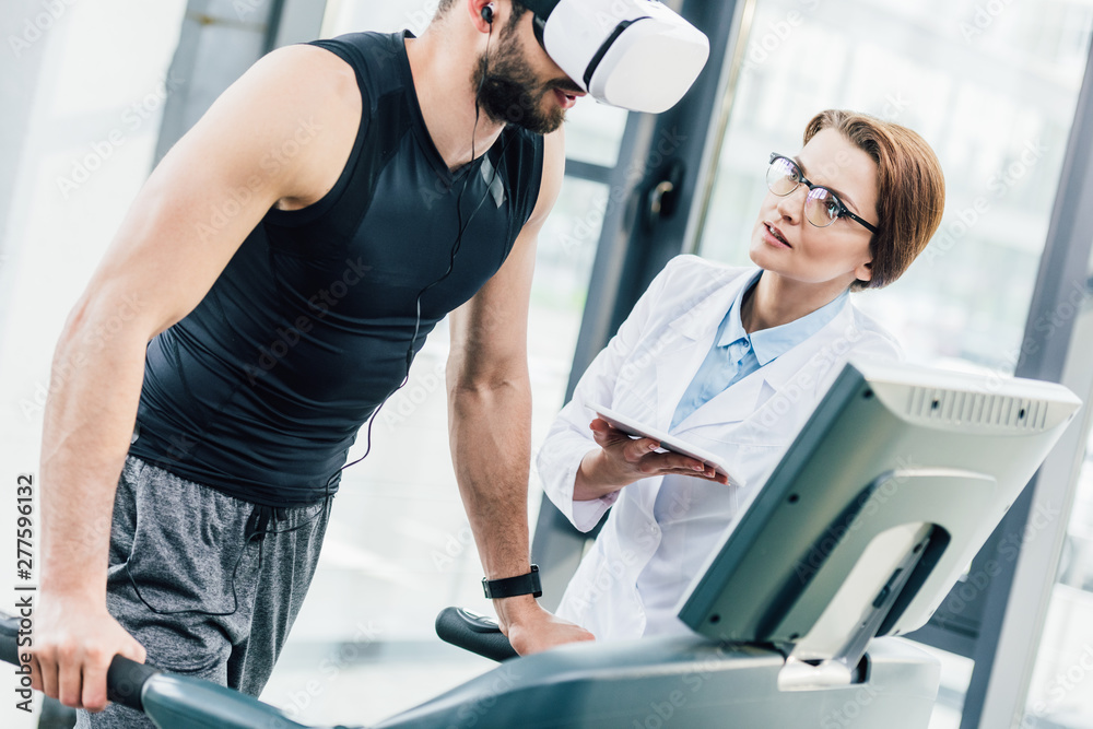 Fototapety, obrazy: sportsman in vr headset training on treadmill near doctor during endurance test in gym