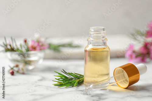 Fototapeta Composition with bottle of natural tea tree oil on white marble table. Space for text obraz