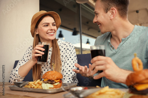 Fototapeta Young happy couple with burgers in street cafe obraz na płótnie