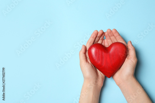 Woman holding heart on blue background, top view with space for text Canvas Print