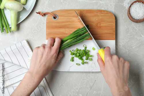 Fotomural  Woman cutting fresh green onion on wooden board at marble table, top view