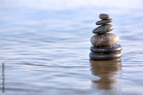 Photo sur Plexiglas Zen pierres a sable Stack of dark stones in sea water, space for text. Zen concept