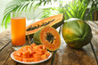 canvas print picture - Fresh papayas and juice on wooden table against blurred background