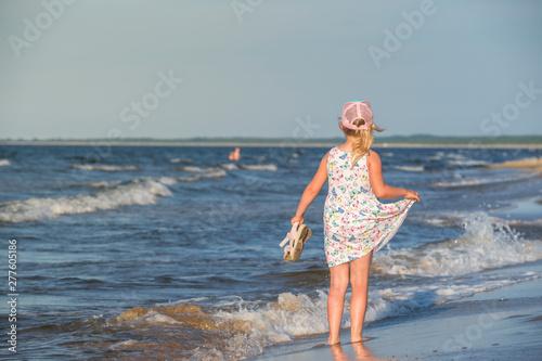 Fototapeta dziewczynka w letniej sukience na morskiej plaży,  obraz