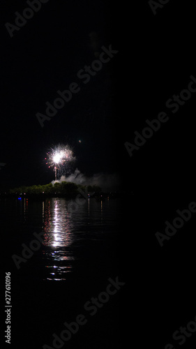 Photo Fireworks with reflections on water of lake on Independence day