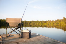 A Chair With Fishing Items On A Wooden Dock On A Lake In Ontario Canada In Summer