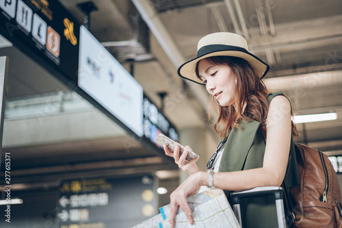 Fotografia  Travelers Asian woman bystander flight schedules on a mobile phone in the airpor