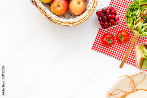 obraz PCV picnic in summer with products, sandwich, salad, fruits and hat on white background top view space for text