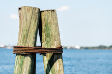 Closeup Of Anchor Wooden Bollard On Boat Pier In Fort Myers Florida With Bay Of Blue Water