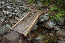 Wooden Bridge Over Rocks In Forest