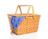 A brown wicker picnic basket on a white background with gingham cloth