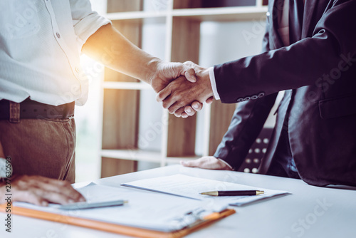 Middle age Asian partner lawyers attorneys shaking hands after discussing a contract agreement done Фотошпалери
