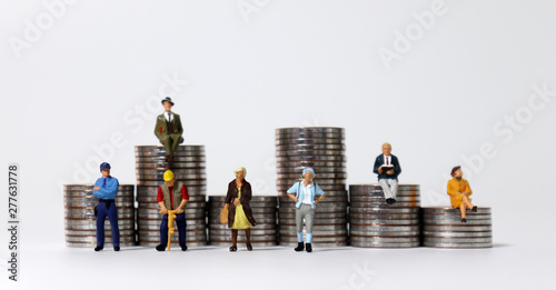 Fotografia  Coin stacks and various miniature people.