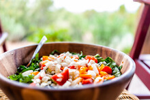 Closeup Of Fresh Salad In Wooden Bowl With Lettuce And Bell Peppers Onions And Bokeh Background Of Rocking Chair In Garden Patio