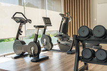 Sport Bike And Dumbbells In Fitness Room