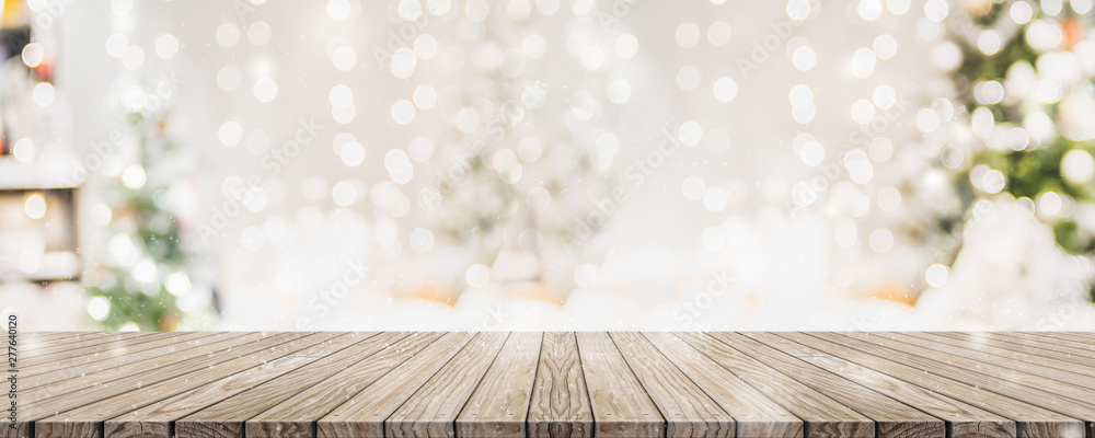Fototapeta Empty woooden table top with abstract warm living room decor with christmas tree string light blur background with snow,Holiday backdrop,Mock up banner for display of advertise product.