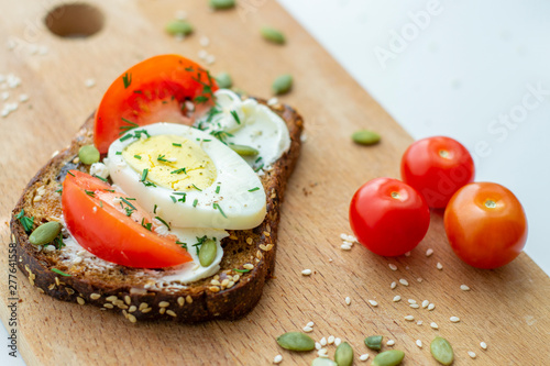 Sandwich with tomato, egg and seeds on whole grain bread. The concept of healthy eating.