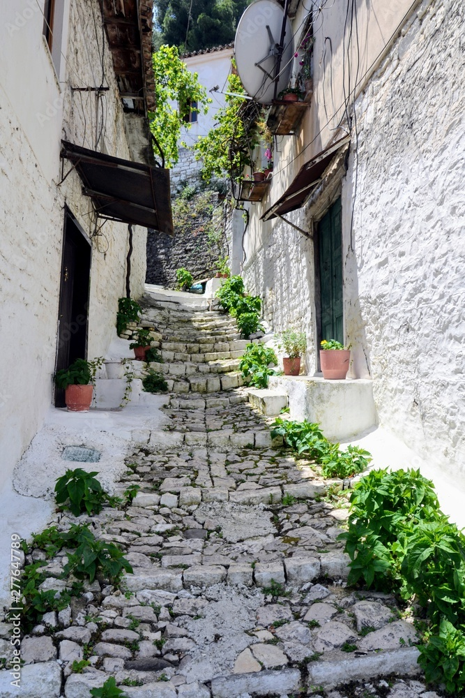 Fototapeta Narrow street with stairs between the old stone houses at district of Mangalem in Berat, Albania. The albanian ancient city of Berat, designated a UNESCO World Heritage Site in 2008.