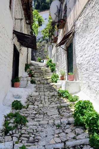 Narrow street with stairs between the old stone houses at district of Mangalem in Berat, Albania. The albanian ancient city of Berat, designated a UNESCO World Heritage Site in 2008.  - fototapety na wymiar