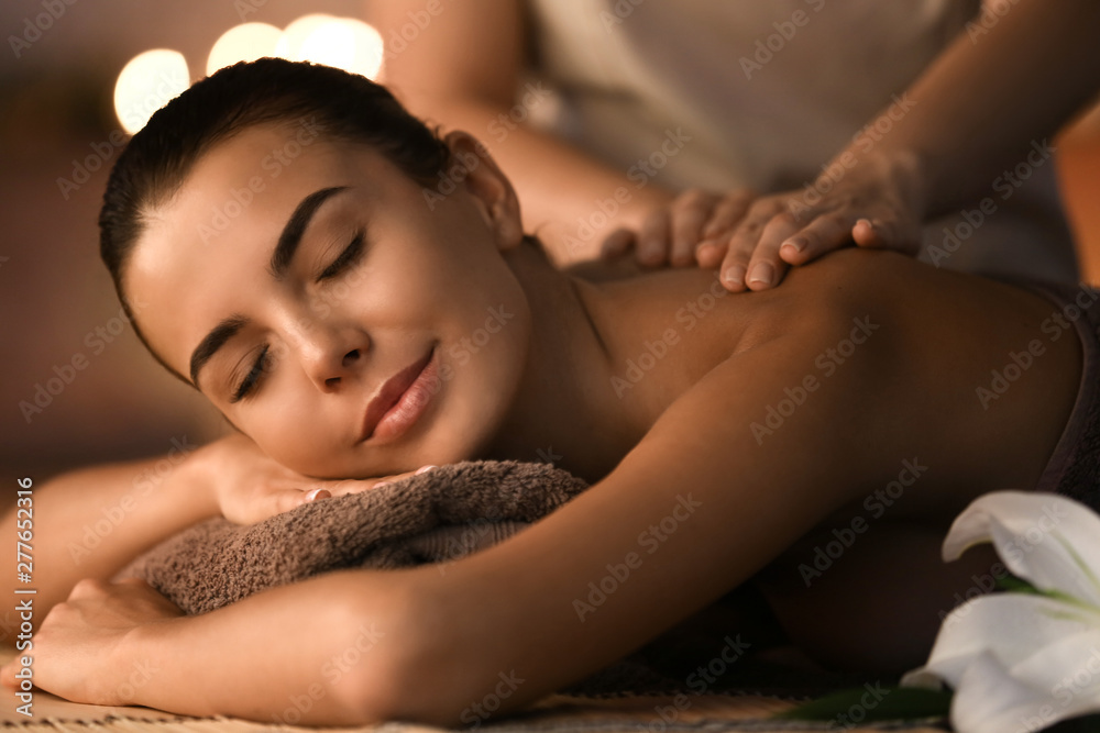 Fototapeta Beautiful young woman receiving massage in spa salon