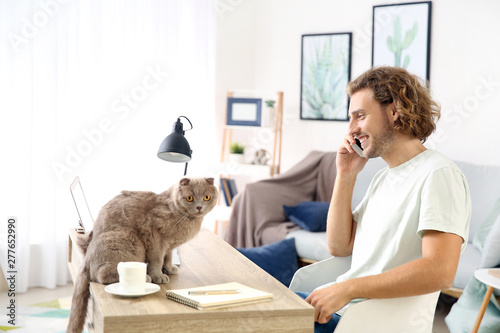 Man with cute funny cat working at home - 277652990