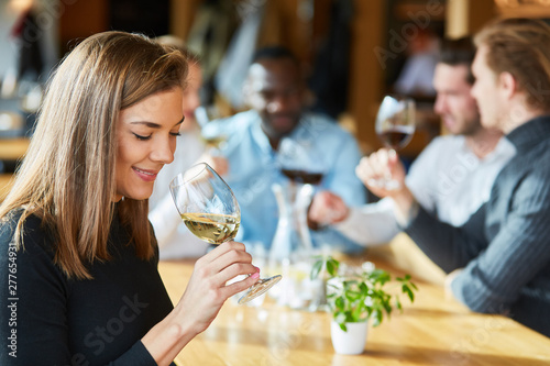 Fototapeta Woman is drinking a glass of wine on a wine tasting