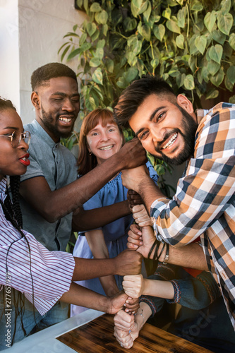 Fotografía  Group of happy multiracial friends thumbs up together.