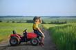 Leinwandbild Motiv Little boy farmer on a tractor among green grain fields