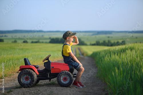 Leinwand Poster Little boy farmer on a tractor among green grain fields