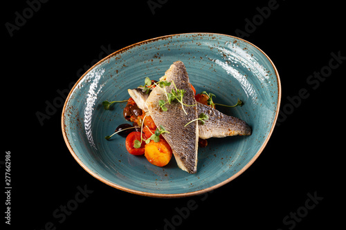 Fototapeta Plate of grilled dorado fillet served with roasted vegetables and tomato sauce isolated at black background
