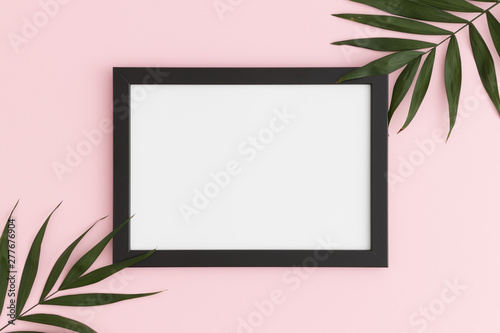 Poster Rose clair / pale Top view of a black frame mockup with palm leaf decoration on a pink background. Landscape orientation.
