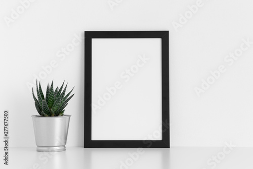 Fototapety, obrazy: Black frame mockup with a cactus in a pot on a white table. Portrait orientation.