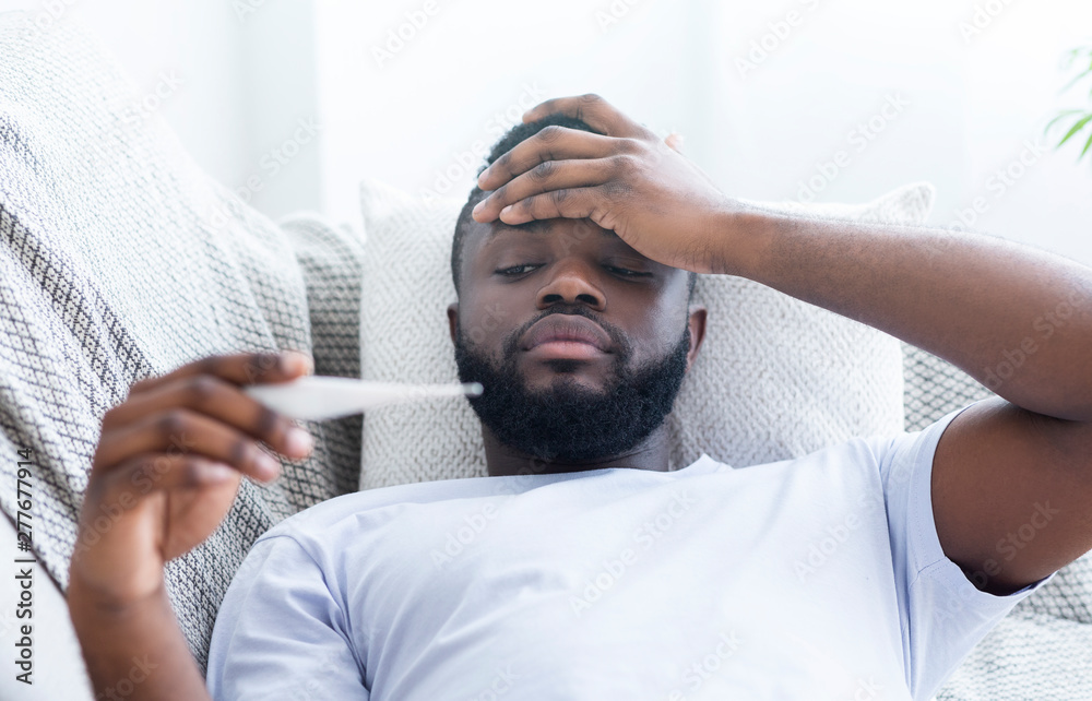 Fototapety, obrazy: African-american man checking his body temperature at home