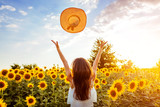 Young woman walking in blooming sunflower field throwing hat up and having fun. Summer vacation