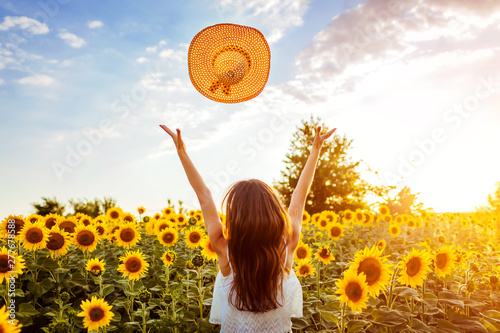 Spoed Foto op Canvas Zonnebloem Young woman walking in blooming sunflower field throwing hat up and having fun. Summer vacation