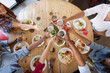 leisure, food and people concept - group of happy international friends eating and clinking glasses at restaurant table