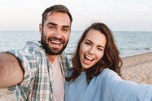 Beautiful Young Smiling Couple Spending Time At The Beach