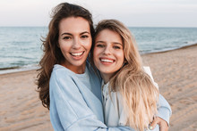 Two Cheerful Smiling Girlfriends Having Fun At The Beach