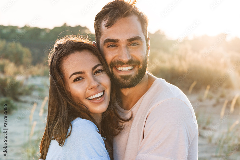 Fototapeta Beautiful young smiling couple spending time at the beach