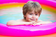 canvas print picture - Child having fun in summertime. Summer holidays and vacation concept. Happy little boy playing in swimming pool outdoor on hot summer day. Children fun.