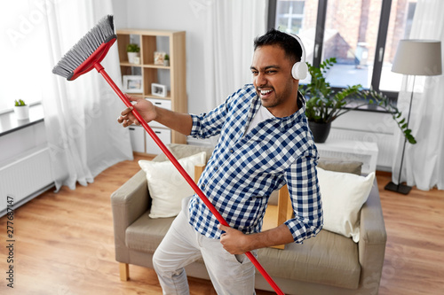 cleaning, housework and housekeeping concept - indian man in headphones with broom sweeping and having fun at home - 277687147