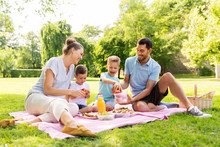 Family, Leisure And People Concept - Happy Mother, Father And Two Little Sons Having Picnic At Summer Park
