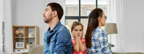 family problem, divorce and people concept - unhappy father, mother and sad little daughter between them at home