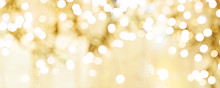 Festive Abstract Defocused Christmas Background. Golden Christmas Lights Sparkle, Beautiful Round Bokeh, Wide Banner Format, Copy Space.