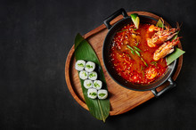 Tom Yum Soup With Maki Roll At Black Background. Tom Yum Is A Traditional Thai Cuisine Spicy Soup With Kaffir Lime, Lemongrass, Galangal, Chili Pepper, Langoustines And Prawns, Mussels
