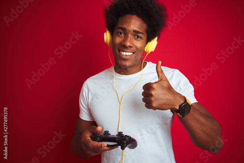 Poster Ecole de Danse Afro gamer man playing video game using joystick headphones over isolated red background happy with big smile doing ok sign, thumb up with fingers, excellent sign