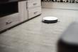 white robot vacuum cleaner in interior on light laminate or parquet