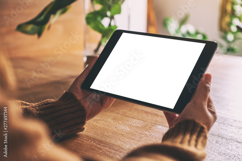 Mockup image of hands holding and using black tablet pc with blank white desktop screen on wooden table