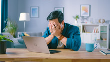 Shot Of An Upset Young Man Covers His Face With Palms In Frustration, While Getting Bad News From Reading Bad News On A Laptop. Upset Man At Home.