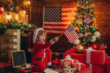 Kid Play American Flag Christmas Tree. Little Boy Santa Hat And Costume Having Fun. American Traditions Concept. Cute Baby Toddler Celebrate Christmas. American Child Cheerful Mood Waving Flag